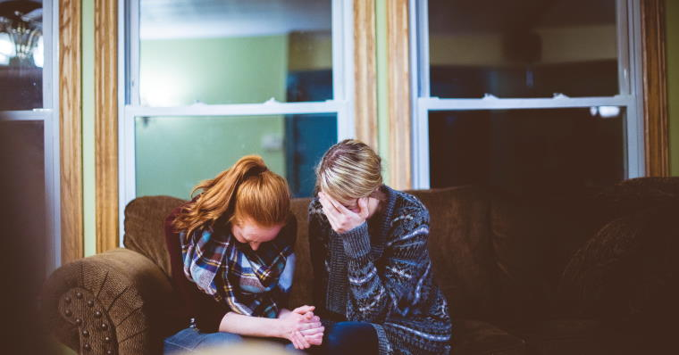 Two people sitting on couch looking down and sad
