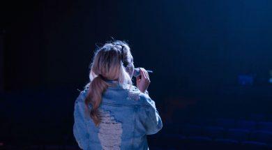 woman-with-microphone-stage-alex-wark-unsplash.jpg