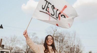 woman-waves-jesus-flag-daniel-gutko-unsplash.jpg